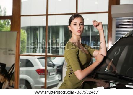 beautiful elegant woman in a green dress standing near a big expensive car - stock photo