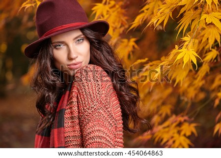 Beautiful elegant woman in a park in autumn - stock photo