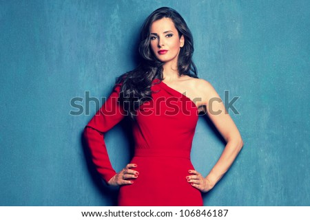 beautiful elegant woman in red dress  with one sleeve on blue wall studio shot - stock photo