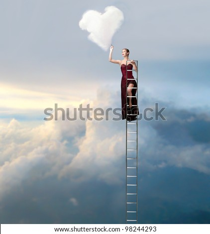 Beautiful elegant woman on a ladder in the sky drawing a heart-shaped cloud - stock photo