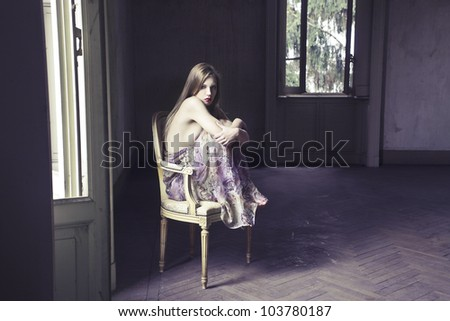 Beautiful elegant woman sitting on a chair in an empty room - stock photo