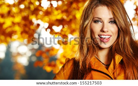 Beautiful elegant woman standing in a park in autumn  - stock photo