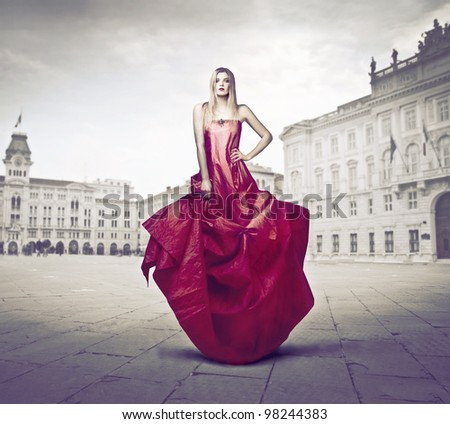 Beautiful elegant woman standing on a town square - stock photo