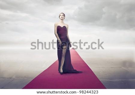 Beautiful elegant woman walking on the red carpet - stock photo