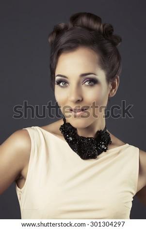 beautiful elegant woman with classic look against dark studio background - stock photo