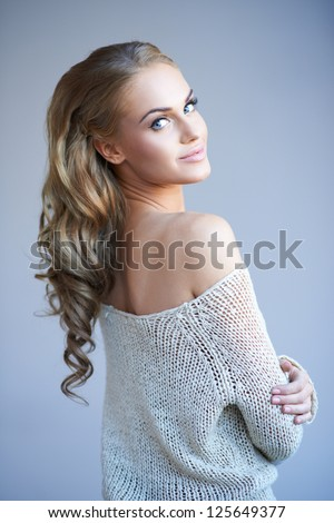 Beautiful elegant woman with long curly blonde hair wearing a stylish off the shoulder top looking back over her shoulder with a smile - stock photo