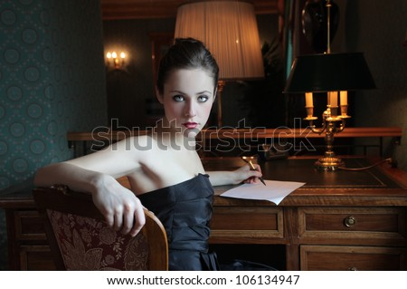 Beautiful elegant woman writing a letter - stock photo