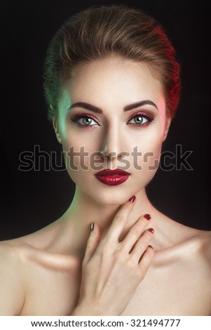 Beautiful  elegant young model with red lips and color evening make-up.Woman Face on dark background.Picture taken in the studio.High fashion look.glamor closeup portrait of  sexy stylish brunette  - stock photo