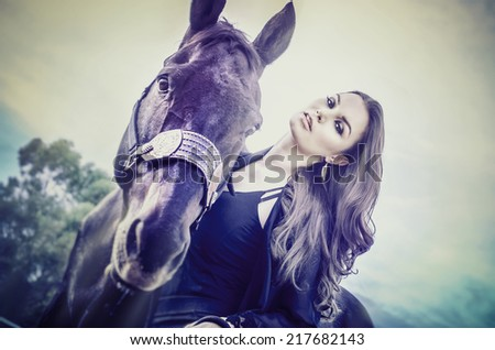 Beautiful elegant young woman and hew horse - stock photo