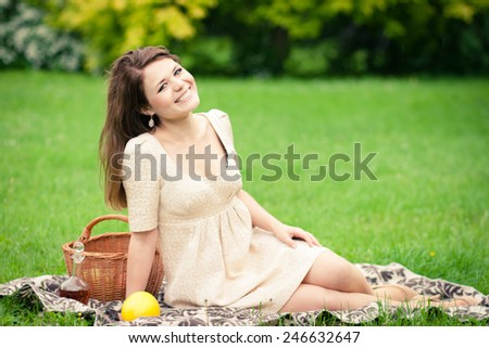 Beautiful elegant young woman picnicing in the park - stock photo