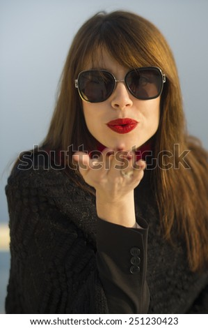 Beautiful elegant young woman wearing sunglasses and red lipstick blowing a kiss. - stock photo