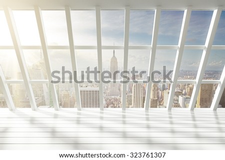 Beautiful empty white loft interior with city view at dawn - stock photo