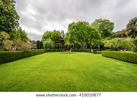 Beautiful English style garden with hedges, & symmetrical type design, with a large open green lawn for parties & open air activities. The garden is designed with European flair, class and tradition. - stock photo