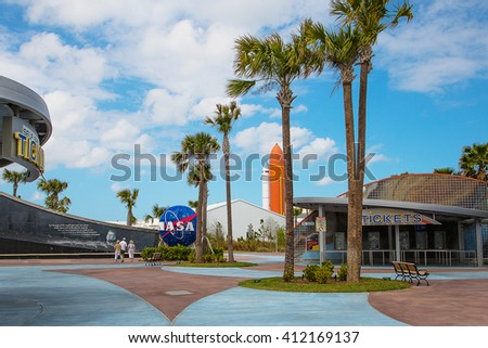 Beautiful entrance to Kennedy space center in Florida with palms NASA logo and space rocket on the background - stock photo