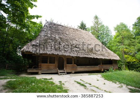 Beautiful ethno rustic house with reed-covered roof in the forest. Summer landscape with a lonely mountain village in the Ukrainian Carpathians. - stock photo