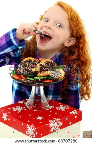 Beautiful Excited Girl Child in Pajamas with a Tray of Holiday Cookies over white background. - stock photo