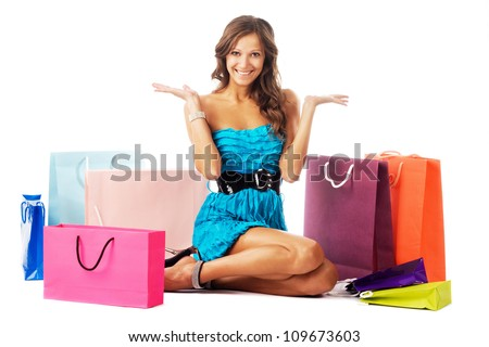 Beautiful excited woman sitting among colorful shopping bags - stock photo