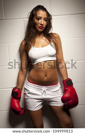 Beautiful exhausted female boxer damp with perspiration posing againt a white tiled wall - stock photo