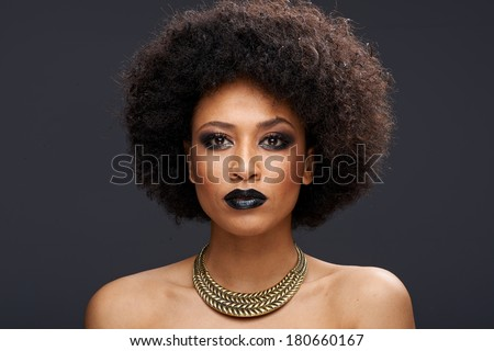 Beautiful exotic African American woman with a curly afro hairstyle wearing dark makeup and a gold choker looking directly at the camera with a serious thoughtful expression - stock photo