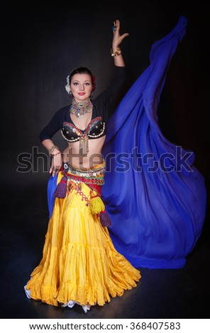 Beautiful exotic belly tribal dancer with blue shawl woman on black background - stock photo