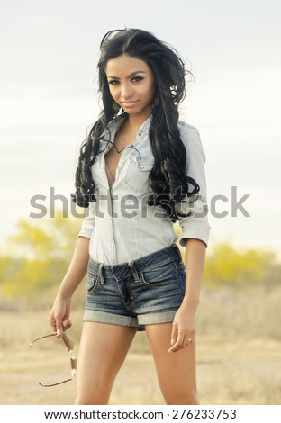 Beautiful exotic ranch girl wearing denim shorts and top - desert south west,USA - stock photo