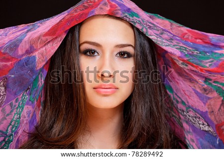Beautiful exotic young woman wearing a colorful veil against a black background. - stock photo