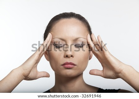 beautiful expressing woman portrait on isolated background massaging her head - stock photo