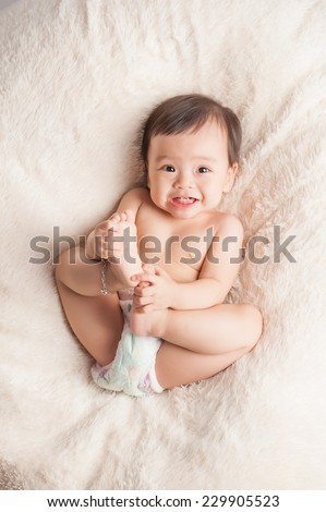 Beautiful expressive adorable happy cute laughing smiling asian baby infant face showing tongue, isolated. - stock photo
