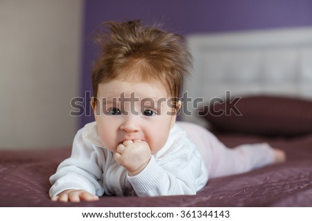 Beautiful expressive adorable happy cute laughing smiling baby infant face. Newborn child relaxing in bed. Nursery for young children. Family morning at home. New born during tummy time with toy bear - stock photo