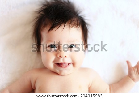 Beautiful expressive adorable happy cute laughing smiling baby infant face showing tongue.  - stock photo