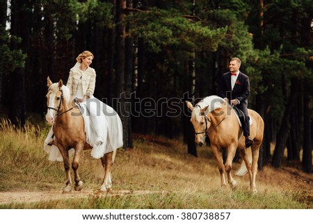 beautiful fabulous happy bride and stylish groom riding horses and lovely looking each other on the background of the autumn forest - stock photo