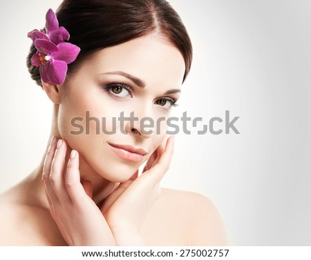Beautiful face of a young and healthy girl with an orchid flower in her hair over grey background - stock photo