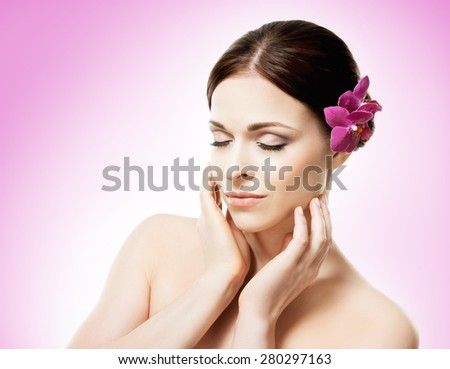 Beautiful face of a young and healthy girl with an orchid flower in her hair over magenta background - stock photo