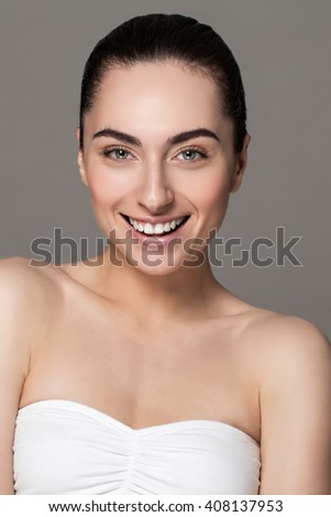 Beautiful face of young adult woman with clean fresh skin and bare shoulders on grey background. - stock photo
