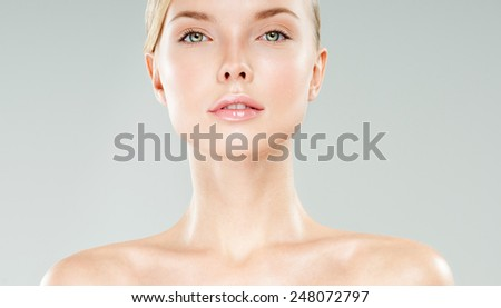 Beautiful face of young adult woman with clean fresh skin. Looking at Camera. - stock photo