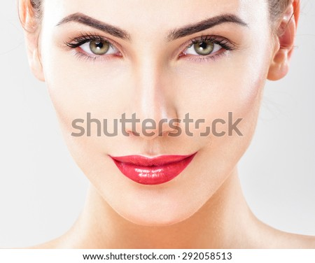 Beautiful face of young adult woman with clean fresh skin. Looking at Camera. Red lipstick. - stock photo