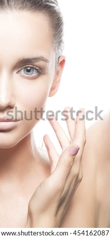 Beautiful face of young caucasian brunette woman with natural lips, make-up and blue eyes isolated on white. Touch her perfect skin. Studio portrait.  - stock photo