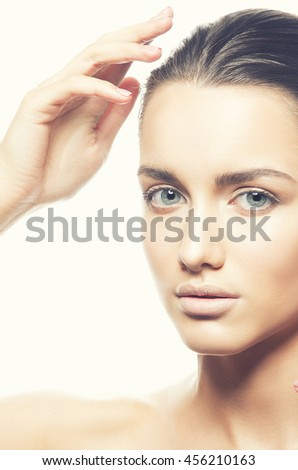 Beautiful face of young caucasian brunette woman with natural lips, make-up and blue eyes isolated on white. Touch her perfect skin. Studio portrait. Toned - stock photo