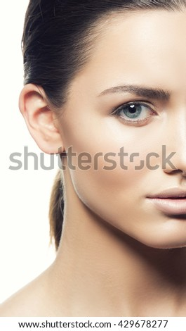 Beautiful face of young caucasian brunette woman with natural lips, make-up, perfect skin and blue eyes isolated on white. Studio portrait. Toned - stock photo