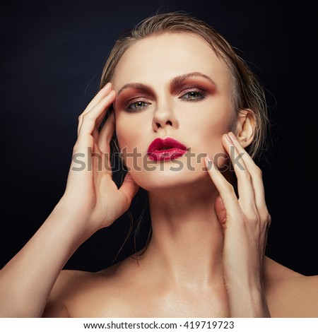 Beautiful face of young caucasian woman with red lips, perfect skin and green eyes isolated on black. Studio portrait. Toned - stock photo