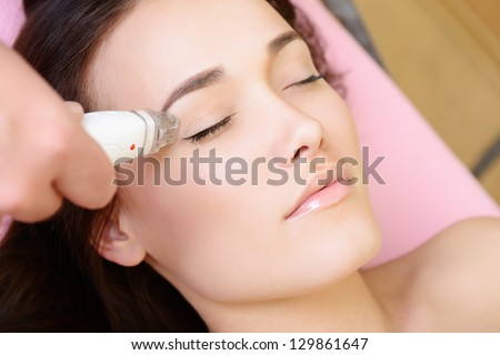 beautiful face of young woman and rejuvenated treatment, lady lies on a couch in a beauty spa getting electrostimulation lifting therapy - stock photo