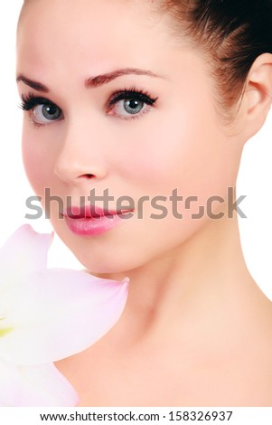 Beautiful face of young woman with big lily.  - stock photo