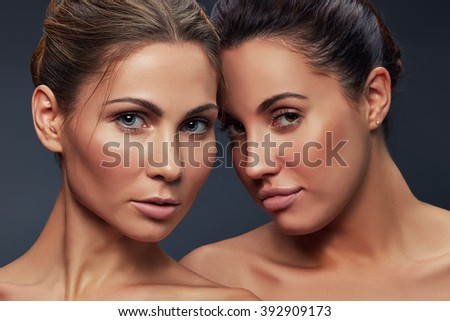 Beautiful faces of young caucasian pair of girls with natural make-up, perfect skin isolated on dark grey background. Studio portrait. Toned - stock photo