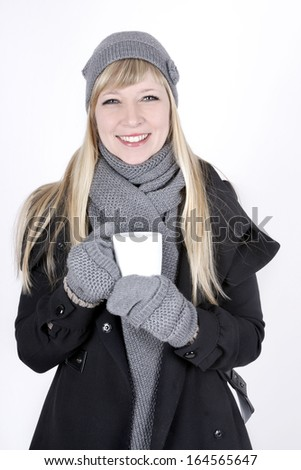 Beautiful fair haired young woman with hot beverage - stock photo