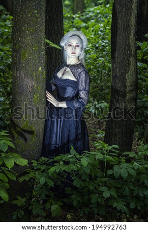 Beautiful fairy girl with white skin alone in the woods. - stock photo