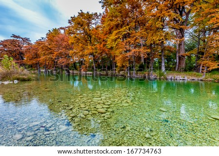 Beautiful Fall Foliage Surrounding the Clear Green Waters of the Frio River, Texas. - stock photo
