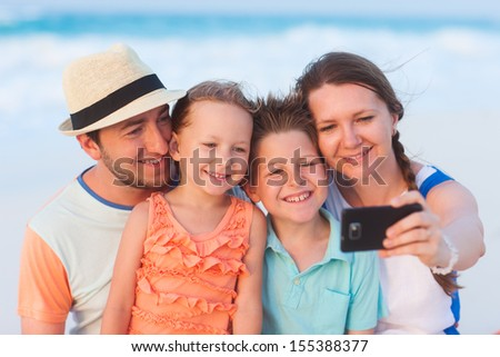 Beautiful family at beach making a self portrait with a mobile phone - stock photo