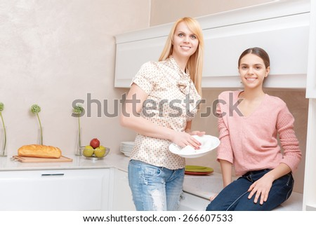 Beautiful family. Attractive blond mother and brunette daughter smiling at the camera and drying dishes at the kitchen - stock photo