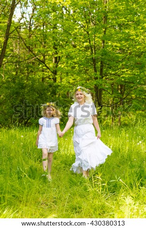 Beautiful family goes hand in hand. Happy family resting on the nature in the summer. Mom and daughter with wreath in the flowers in the park - stock photo