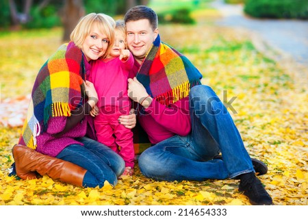 Beautiful family keep warm under a blanket in the autumn park. Fun and games in nature. - stock photo
